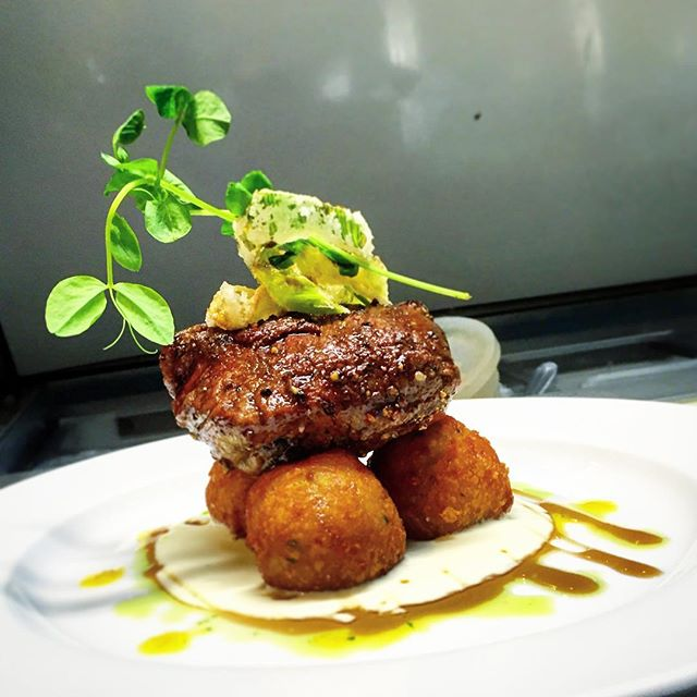 Simple and elegant Filet au Poivre. House aged and cut tenderloin, herbed gruyere pommes dauphine, fried leeks, and cognac cream sauce.